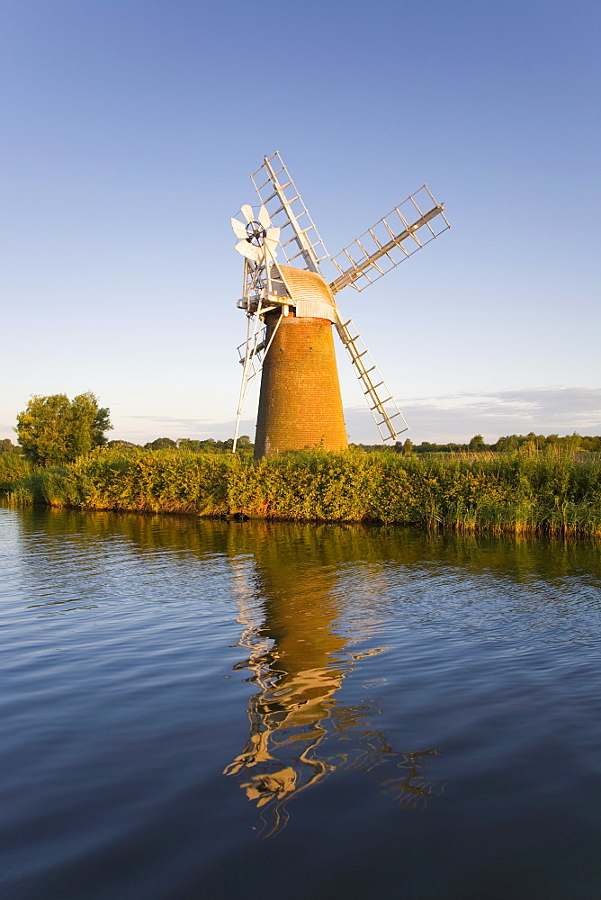Turf Fen windmill reflected in the River Ant at sunrise, Norfolk Broads, How Hill, near Ludham, Norfolk, England, United Kingdom, Europe