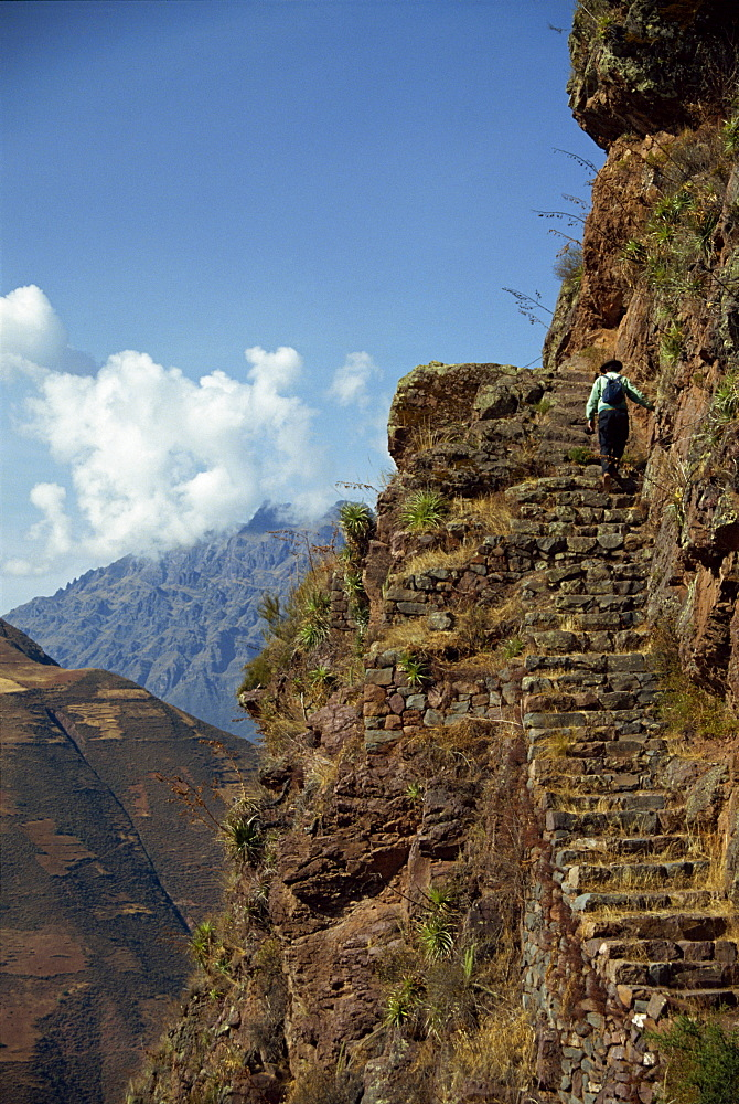 A walker climbs the steps on a narrow path along the edge of a cliff at an Inca site in the Urubamba Valley, Pisac, Peru, South America