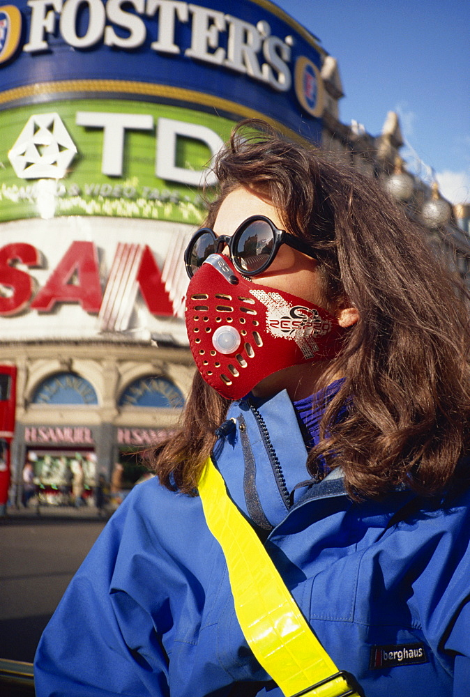 Female cyclist wearing a carbon filtered pollution mask, Piccadilly Circus, London, England, United Kingdom, Europe