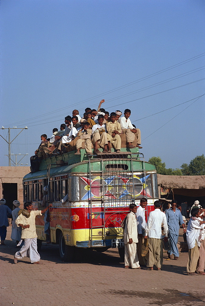Overloaded bus with men riding on the roof near Multan in Pakistan, Asia