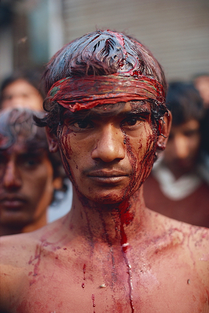 Portrait of a man with head wounds from beating himself with a knife, the bleeding stopped by a headband, during Moharran in Lahore, Punjab, Pakistan, Asia