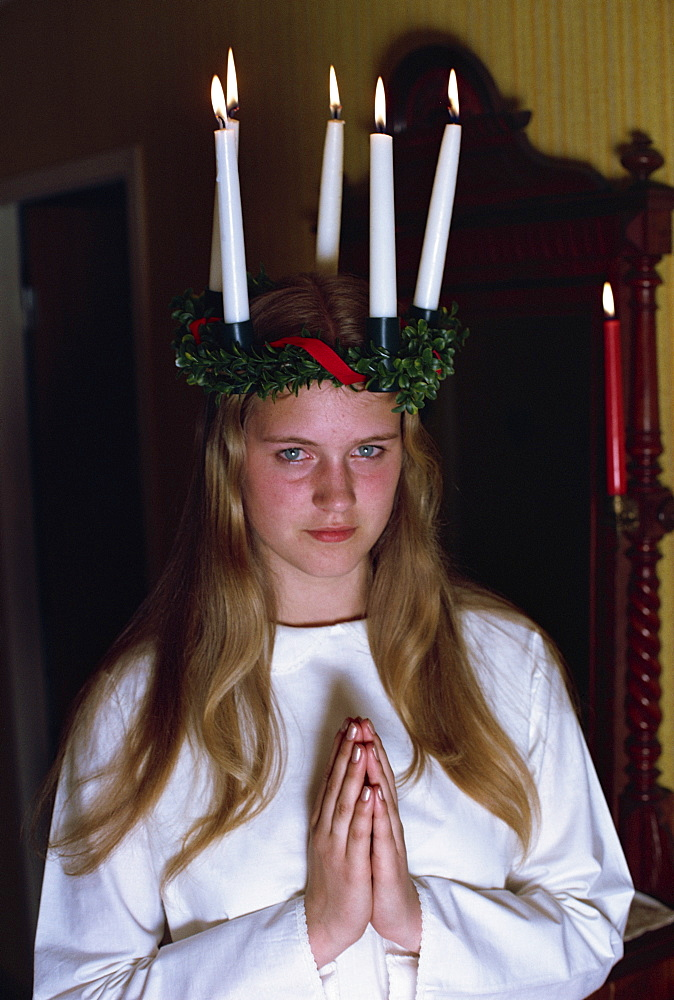 Teenage girl praying in traditional costume, for Santa Lucia Day 13, marking the shortest day of the year, a very important Swedish day, Gothenburg, Sweden, Scandinavia, Europe