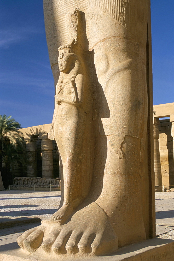 Statue of wife at the feet of Ramses II (Ramses the Great), Temple of Karnak, UNESCO World Heritage Site, Luxor, Egypt, North Africa, Africa