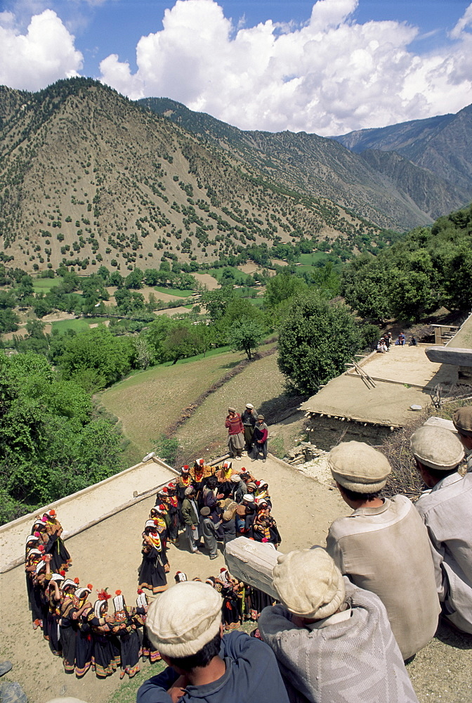 Men watching Kalash women dancing, Spring Festival, Joshi, Bumburet Valley, Pakistan, Asia