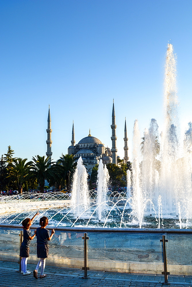 Two young Turkish girls pointing to the Blue Mosque, UNESCO World Heritage Site, with fountains in foreground, Istanbul, Turkey, Europe