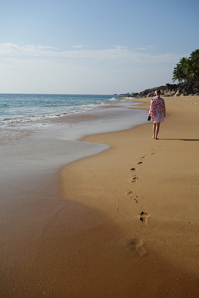 Woman walking leaving footprints on deserted beach, Niraamaya, Kovalam, Kerala, India, Asia