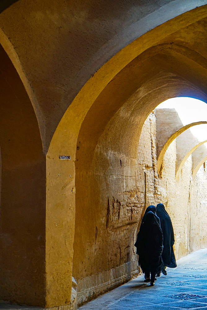 Three women in chadors hurrying down typical vaulted alleyway, Yazd, Iran, Middle East