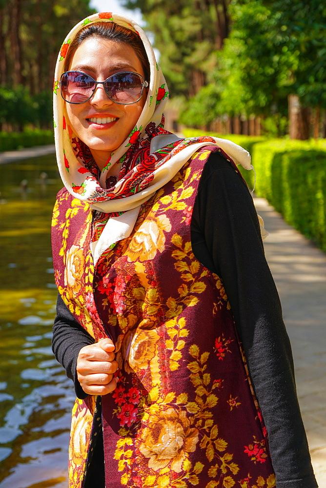 Young Iranian woman in fashionable modern clothes, Bagh-e Dolat garden, Yazd, Iran