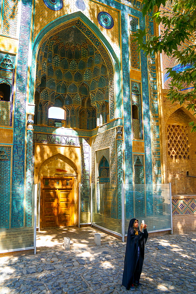 Young Iranian girl in chador taking picture in front of Jameh Mosque, Natanz, Iran, Middle East