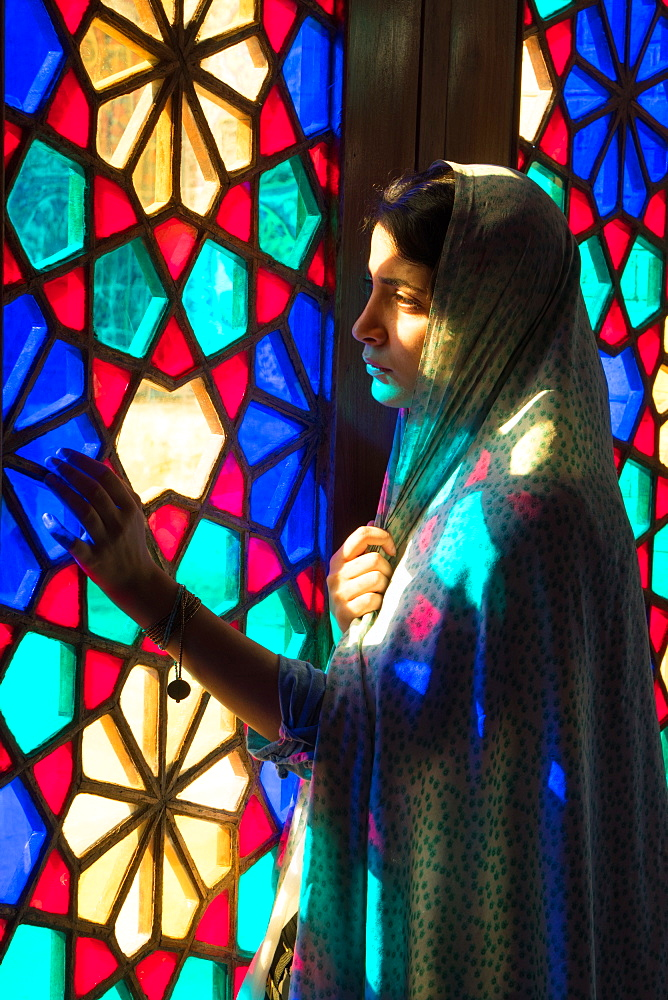Worshipper at stained glass window of Prayer Hall, Nasir-al Molk Mosque, Shiraz, Iran, Middle East