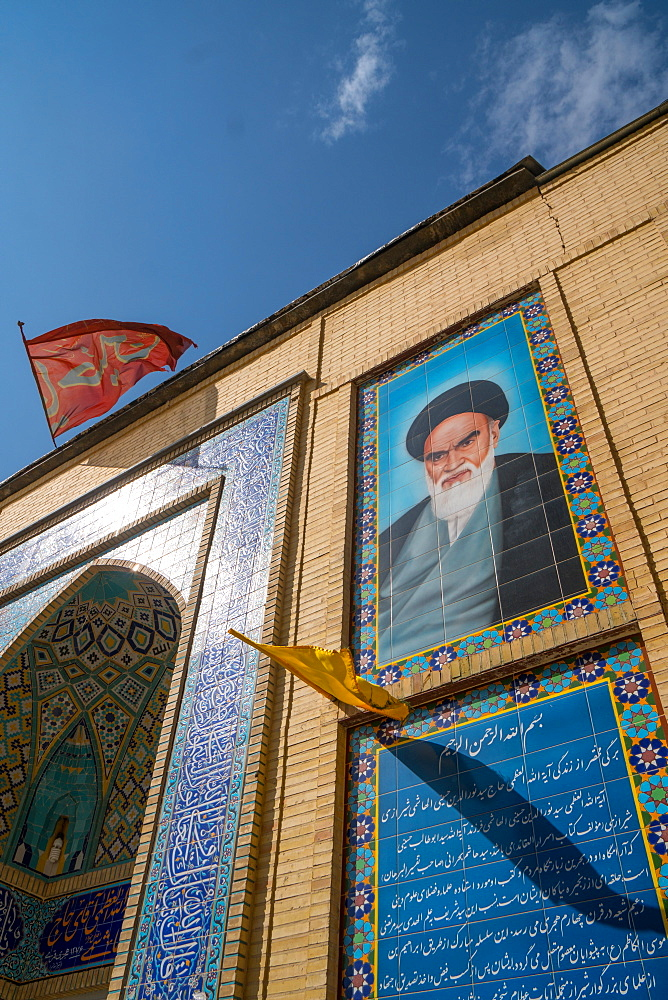 Imam Khomeini looks down from the facade of a small mosque in the backstreets, Shiraz, Iran, Middle East