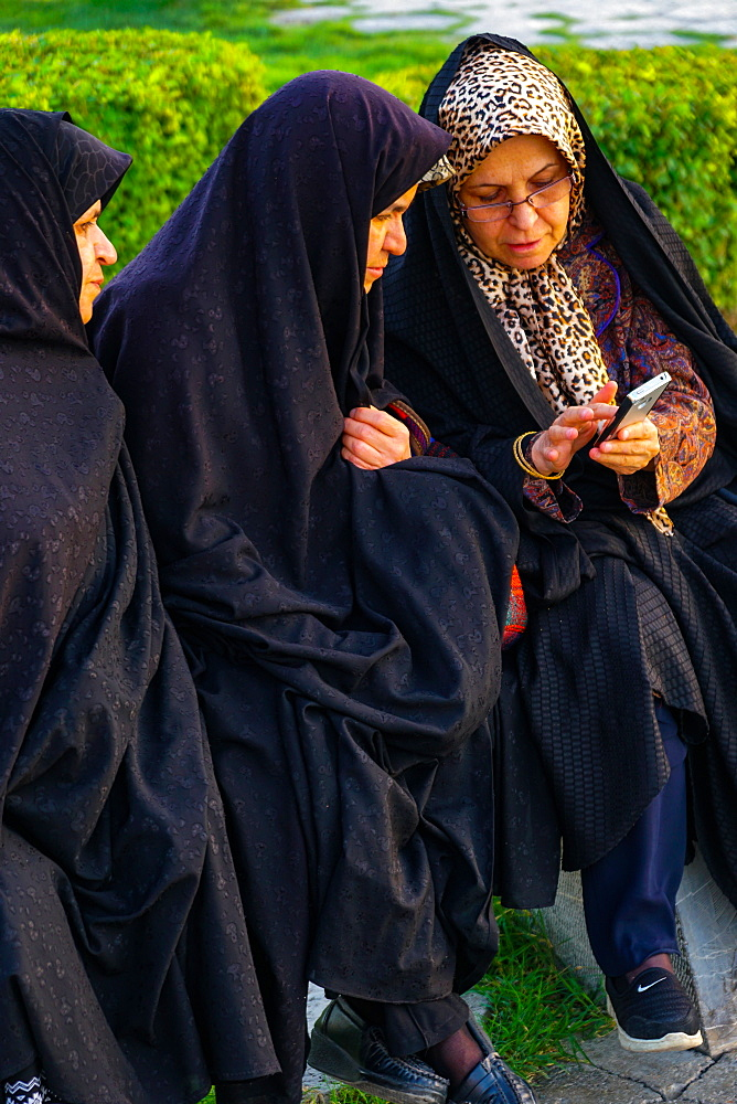 Three old Iranian women transfixed by mobile communication, Isfahan, Iran, Middle East
