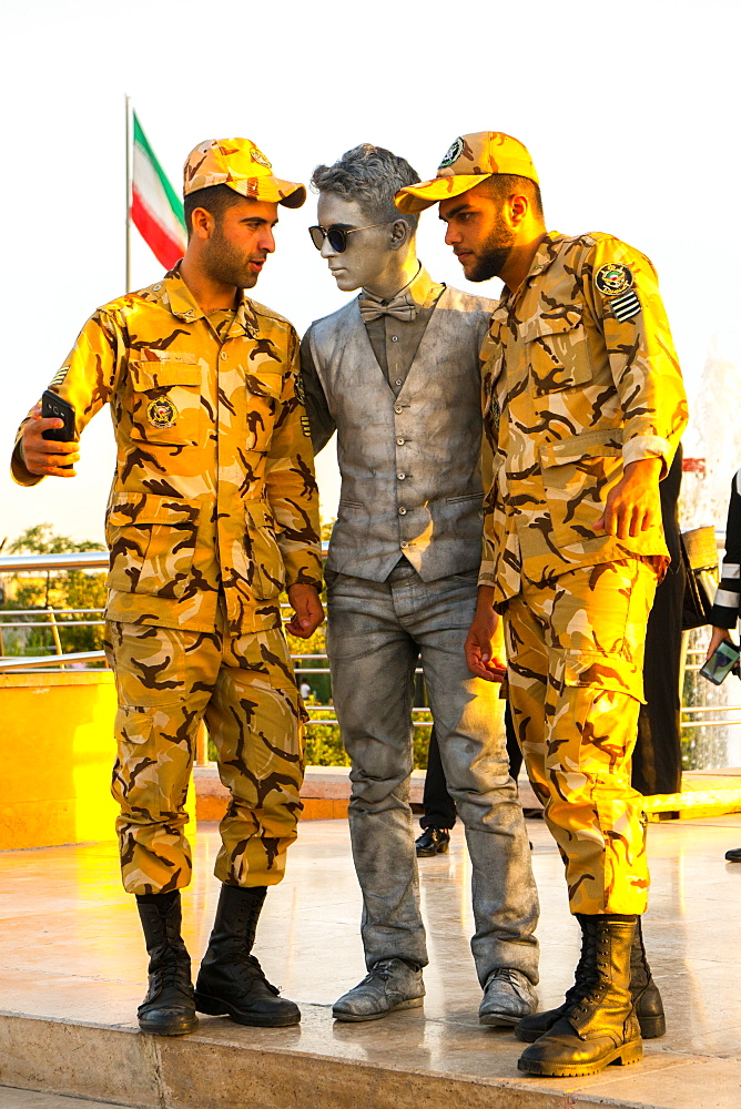 Two soldiers taking a selfie with a street performer, Tehran, Iran, Middle East