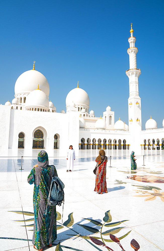 Tourists, fully covered as required by religious rules, photographing the interior of Sheikh Zayed Grand Mosque, Abu Dhabi, United Arab Emirates, Middle East - 450-4222
