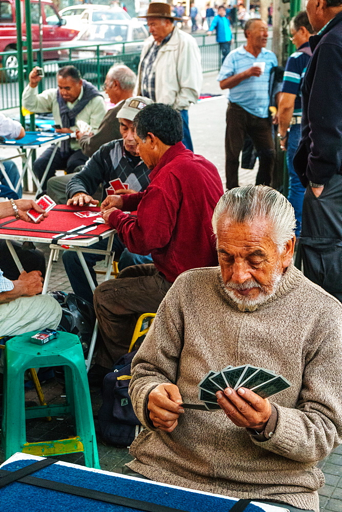 Card players gather out in public by the main bus station, Valparaiso, Chile, South America