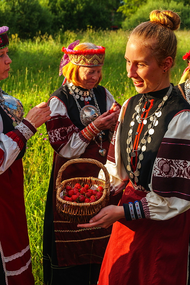 Seto girl offers wild strawberries to friends, Feast Day, Uusvada, Setomaa, SE Estonia, Europe - 450-4276