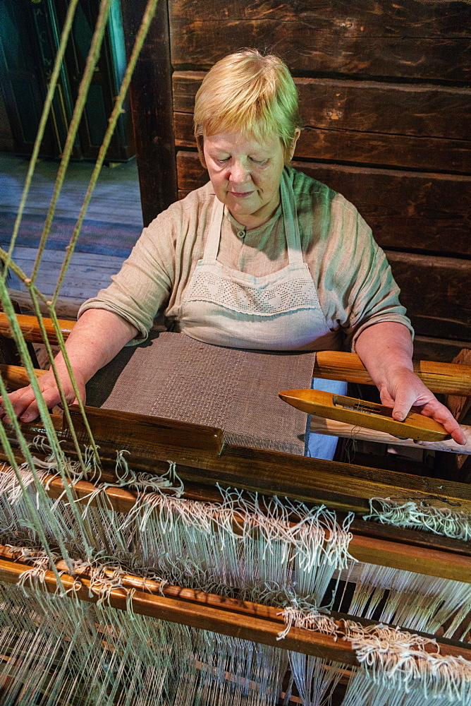 Weaver at work in 19th century house, Latvian Ethographic Open Air Museum, Riga, Latvia, Europe