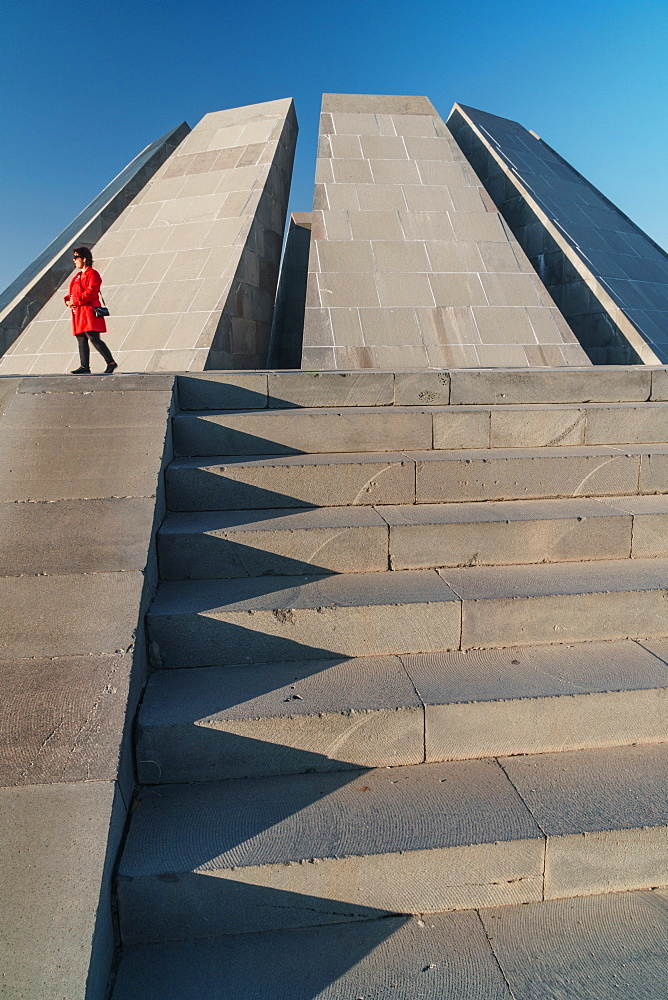Woman in red walks past Armenian Genocide Memorial building, Yeravan, Armenia, Central Asia, Asia