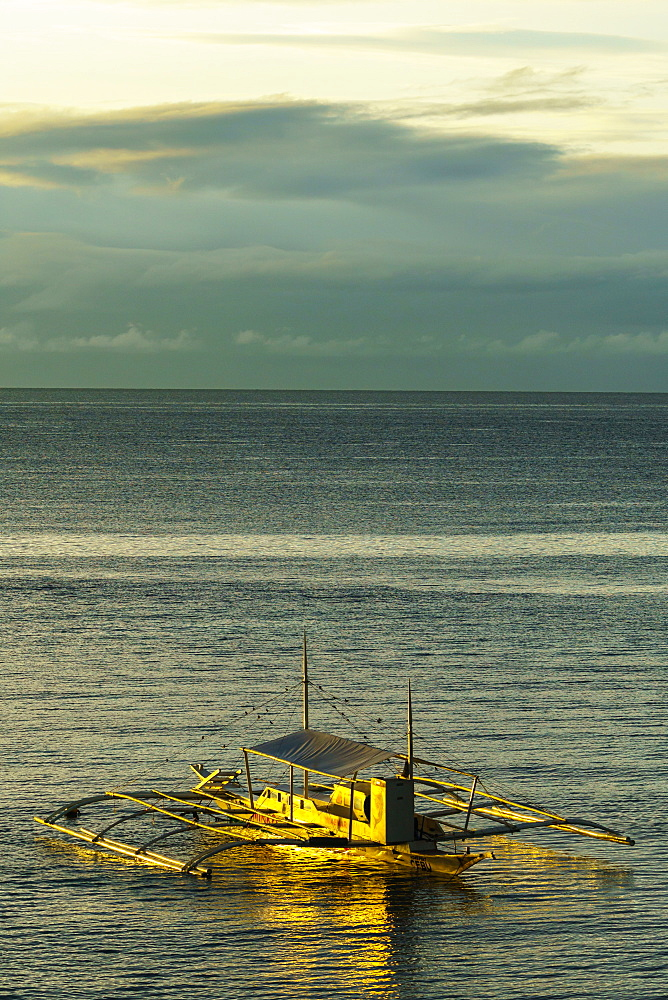 A lone bangka (outrigger canoe) bathed in warm dawn light berthed by Panglao Beach, Bohol Island, Philippines, Southeast Asia, Asia - 450-4318