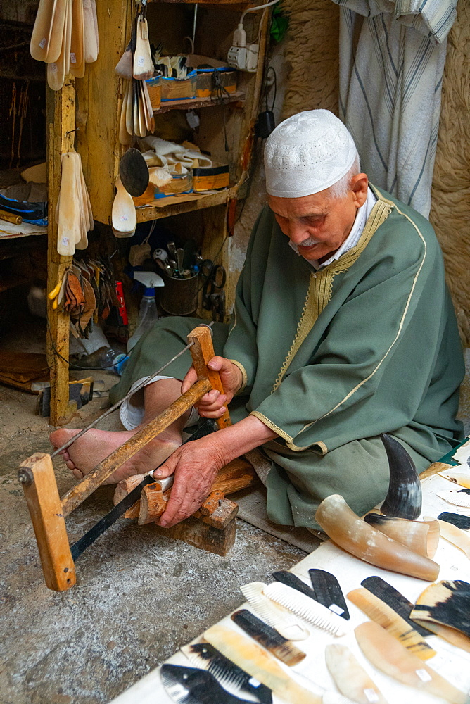 Man saws horn to make combs in an alleyway in the Old City (Medina) of Fez, UNESCO World Heritage Site, Morocco, North Africa, Africa - 450-4386