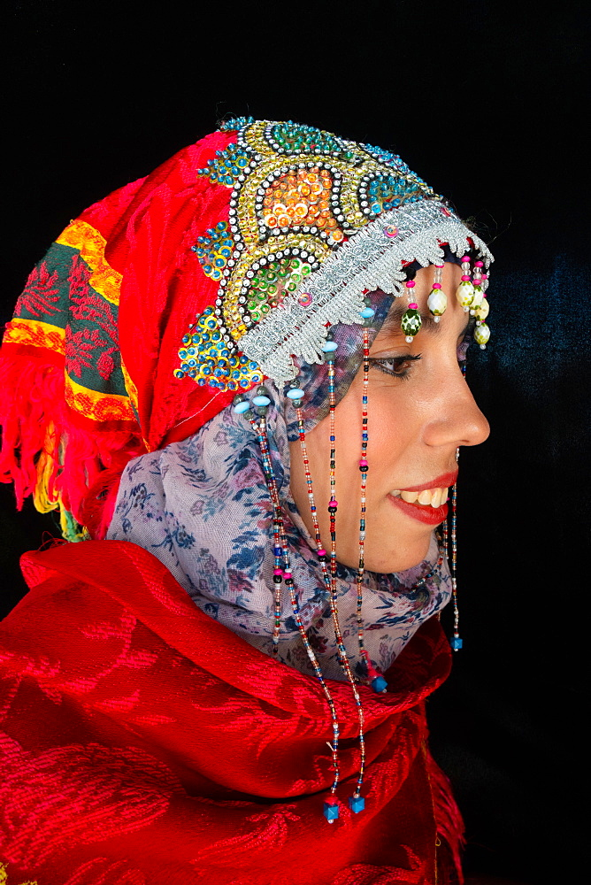 Close-up side portrait of beautiful young Moroccan woman in traditional Berber dress, in Chefchaouen, Morocco, North Africa, Africa