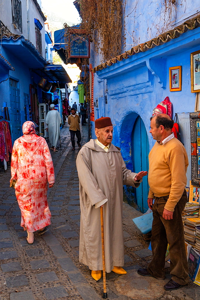 Street scene, old man with stick and red fez (hat) stops to talk with a the owner of a bookshop, Chefchaouen, Morocco, North Africa, Africa
