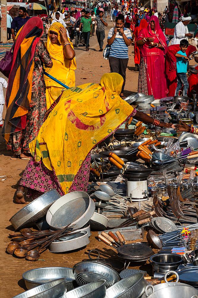 Rajasthani women in brightly coloured traditional clothing shopping for kitchen utensils, Pushkar Fair, Pushkar, Rajasthan, India, Asia - 450-4429