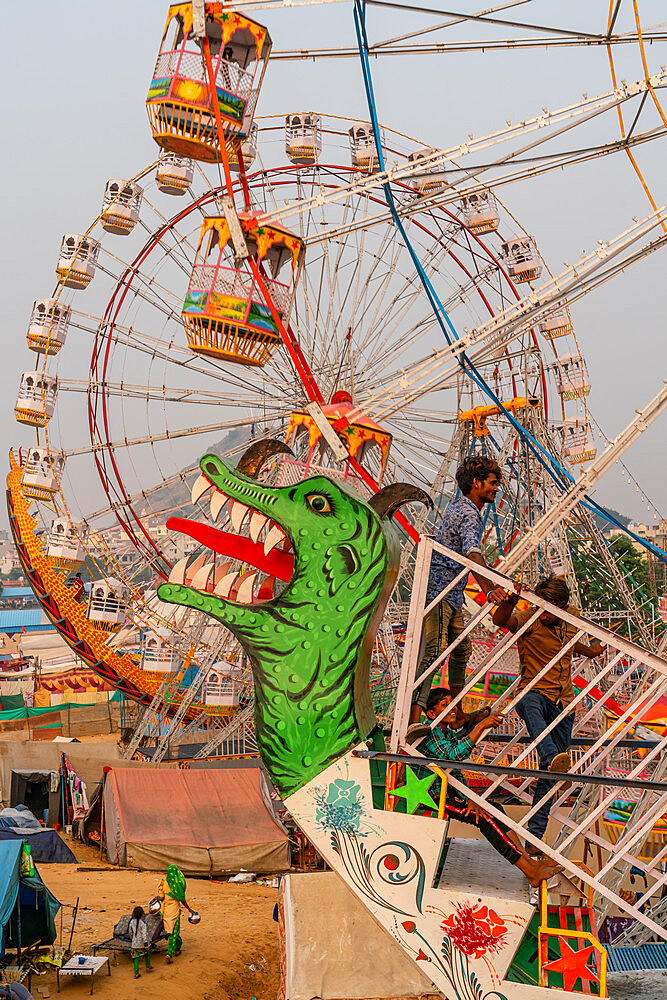 Fairgoers wait for a a swinging gondola to start with two Ferris wheels in the background, Pushkar Fair.