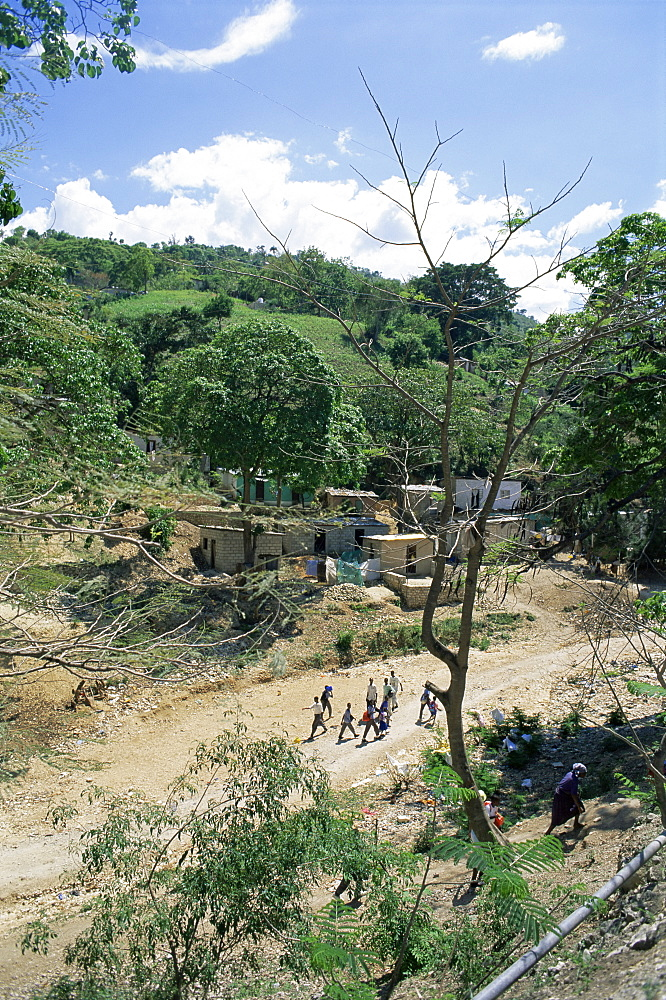 Houses and people walking in dry river bed caused by erosion, near Petionville, Haiti, West Indies, Central America