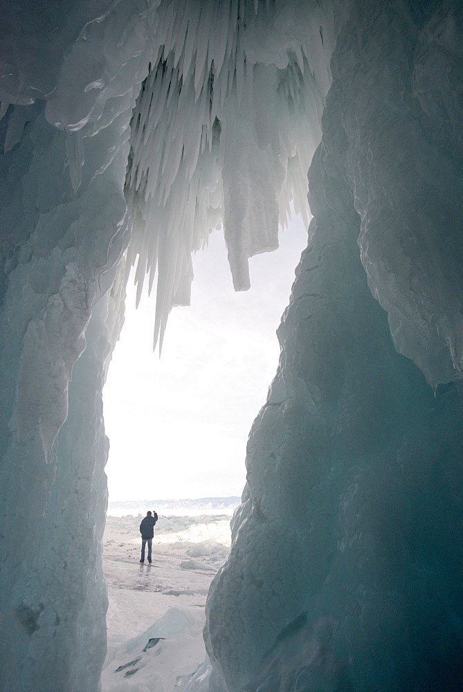 Tourist framed in the frozen mouth of ice cave, with icicles formed on roof of caves at Olkhon Island as the waves freeze in winter, Lake Baikal, Irkutsk Oblast, Siberia, Russia, Eurasia