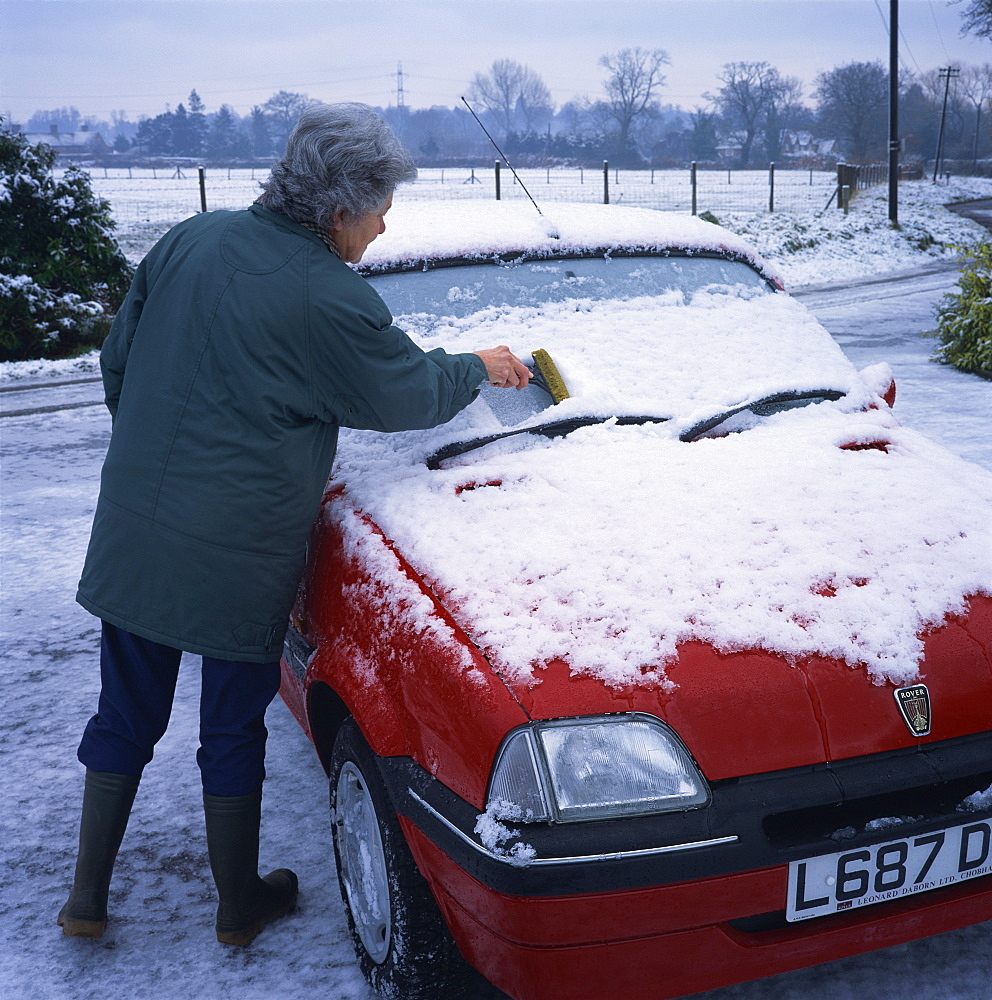 Woman scraping snow off the windscreen of a car in winter, United Kingdom, Europe