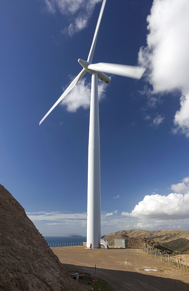One of the turbines with a person for scale, West Wind wind farm of Meridian Energy at Makara, Wellington, North Island, New Zealand, Pacific