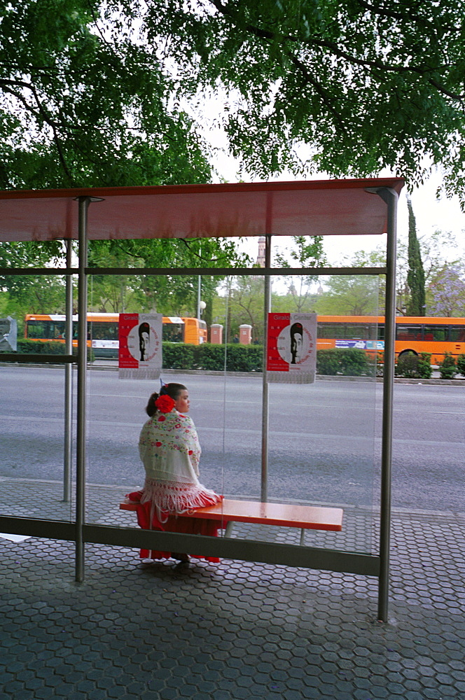 Seville - Spain - The Feria de Abril - Seville Fair - A girl in traditional costume waiting at a bus stop