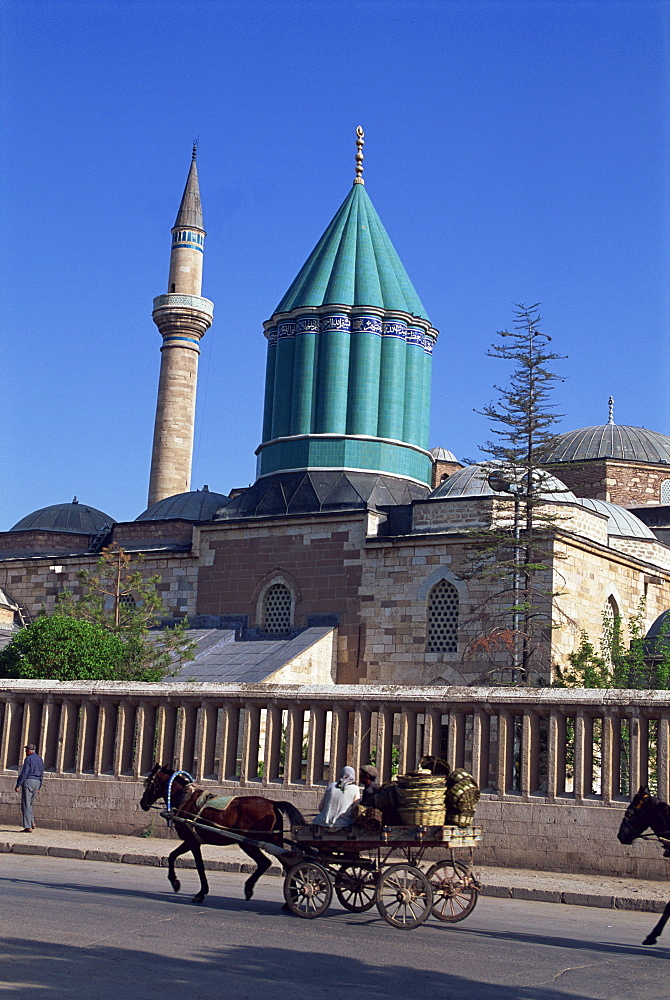 Horse and cart passes the Mevlana Tekke Museum with its green tower and minaret, formerly the monastery, or tekke, of the Whirling Dervishes, at Konya, Anatolia, Turkey, Asia Minor, Eurasia