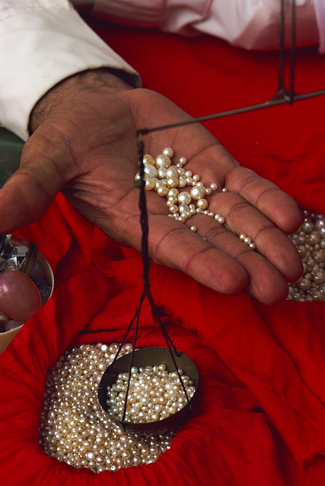 Close-up of hand displaying pearls with weighing scales, in the pearl souk, Manama, Bahrain, Middle East
