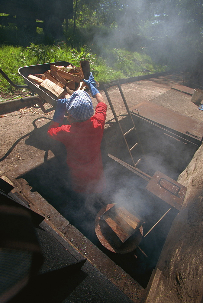 Stoking the smokehouse furnaces for smoking salmon, Scotland, United Kingdom, Europe - 508-47107