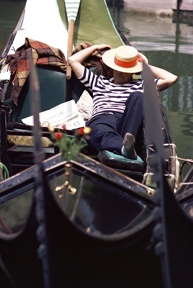 Gondolier relaxing in gondola, Venice, Veneto, Italy, Europe