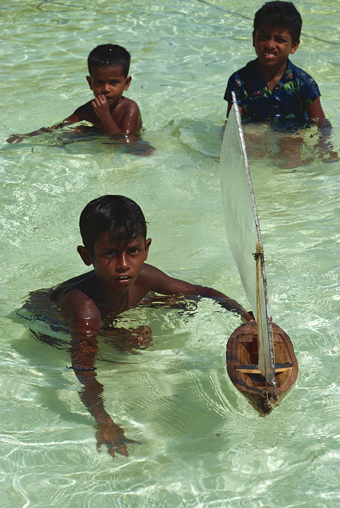 Boys with toy boat, Maldive Islands, Indian Ocean, Asia