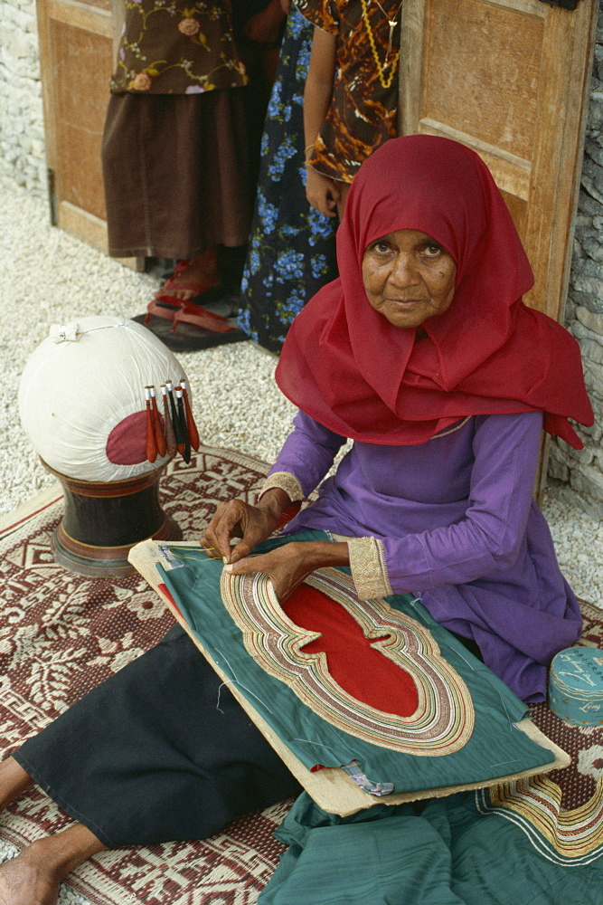 Woman sewing on a collar, Maldive Islands, Asia