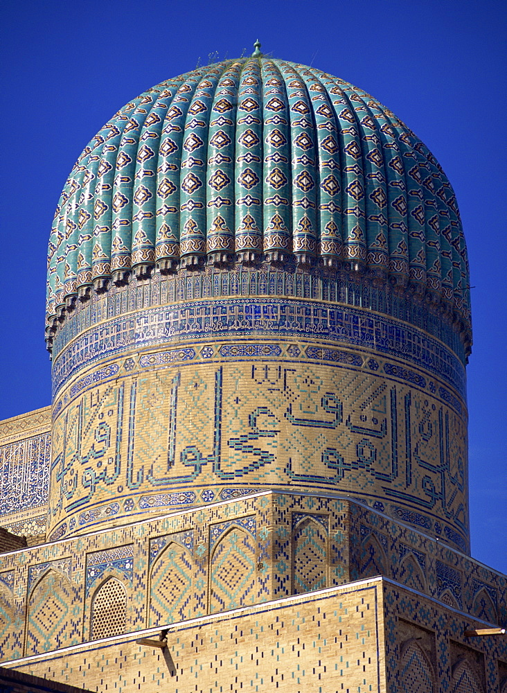 The ribbed dome, tiles and Arabic script on the Bibi Khanym Mosque in Samarkand, Uzbekistan, Central Asia, Asia