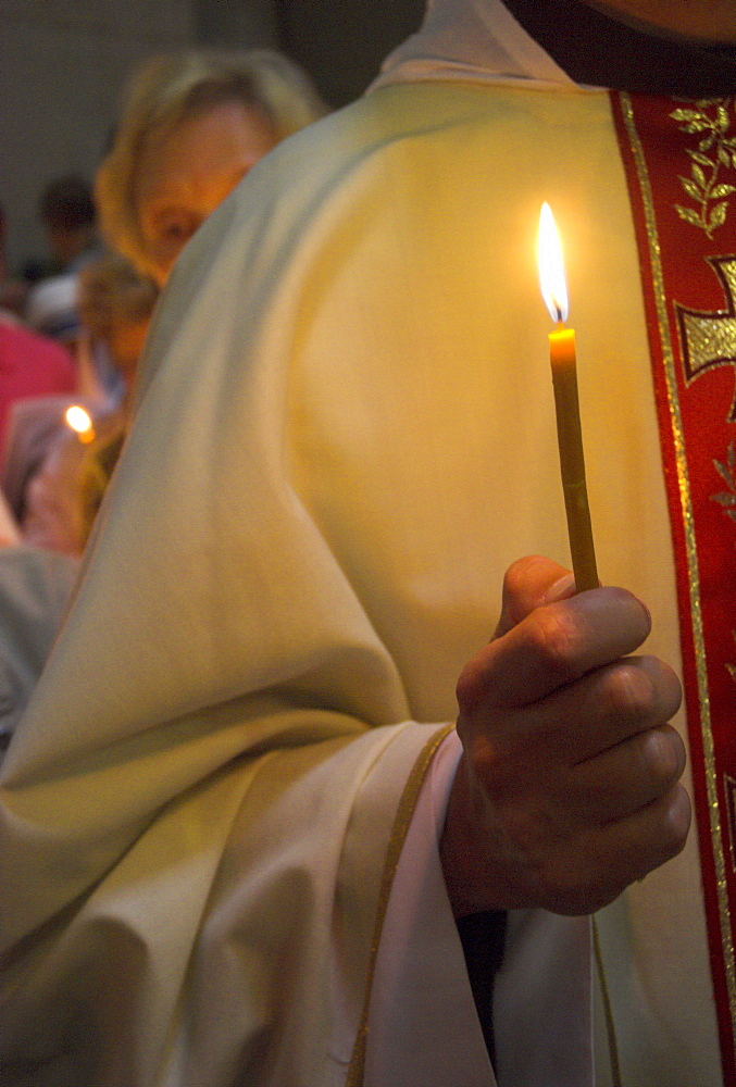 Close-up of a priest's hand holding a candle during Mass in Easter week, Church of the Holy Sepulchre, Old City, Jerusalem, Israel, Middle East