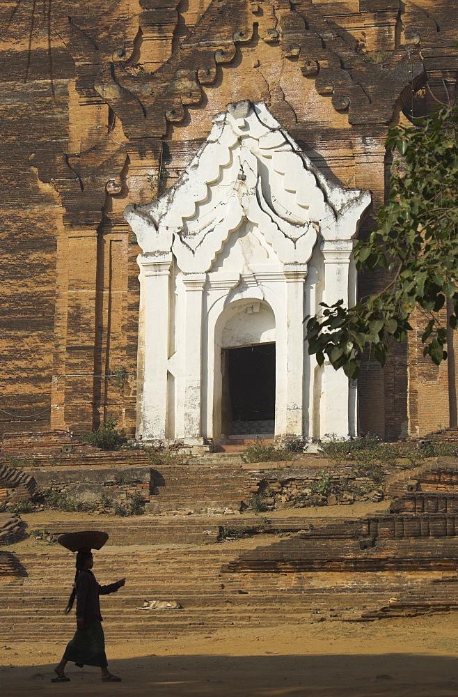 Silhouette of a woman with tray on her head walking past stupa entrance, Mingun Paya, near Mandalay, Myanmar (Burma), Asia