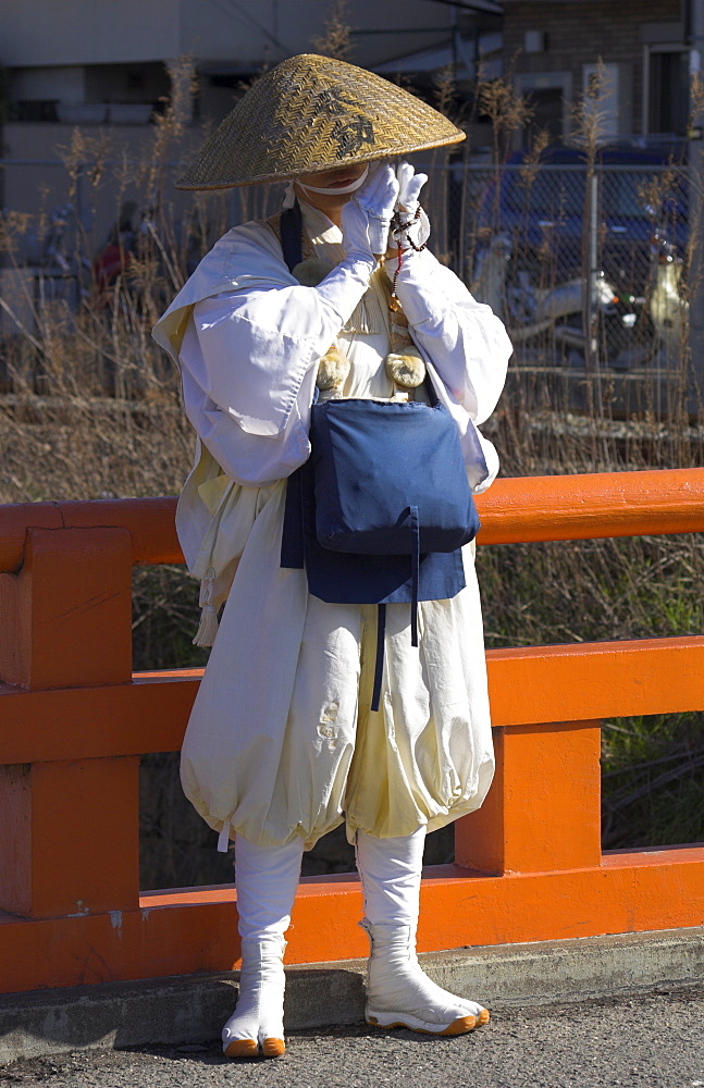 Pilgrim wearing traditional hat and white clothes standing on a bridge and praying, near Fushimi Inari Taisha shrine, Kyoto, Kansai, Honshu, Japan, Asia