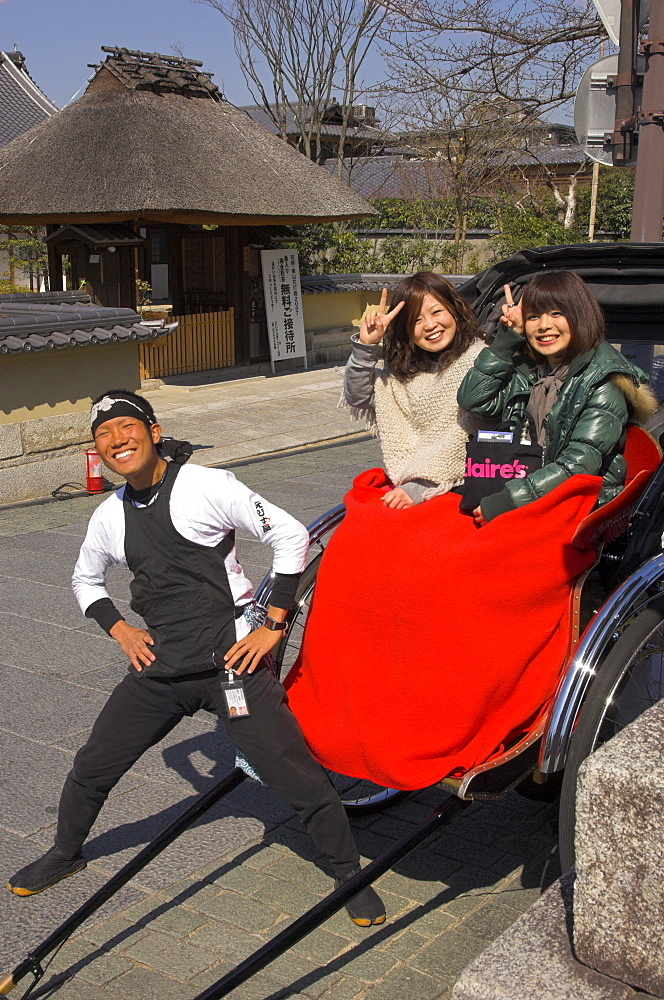 Rickshaw driver and two young Japanese women in rickshaw with red blanket waving at camera, Maruyama park, Higashiyama neighbourhood, Kyoto, Kansai, Honshu, Japan, Asia