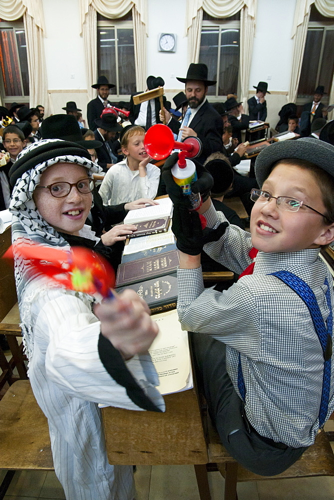 When Haman's name is read out during the public chanting of the Megillah in the synagogue, which occurs 54 times, the congregation engages in noisemaking to blot out his name, Purim Festival, Ramat Beit Shemesh, Israel, Middle East