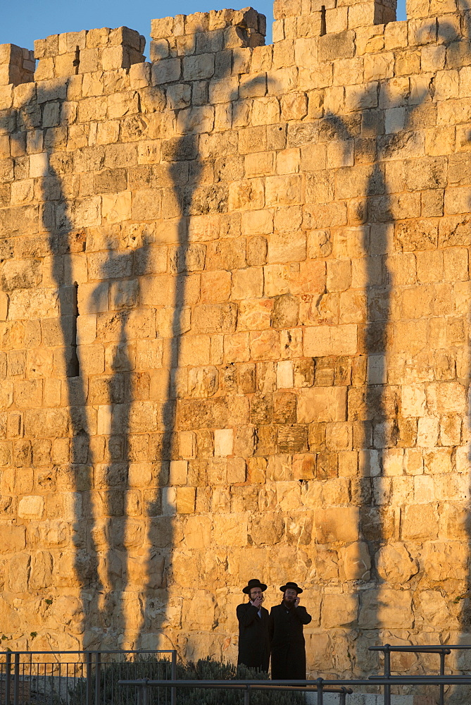 Two Orthodox Jewsh with palm tree shadows in background along the Old City walls, Jerusalem Old City, Israel, Middle East