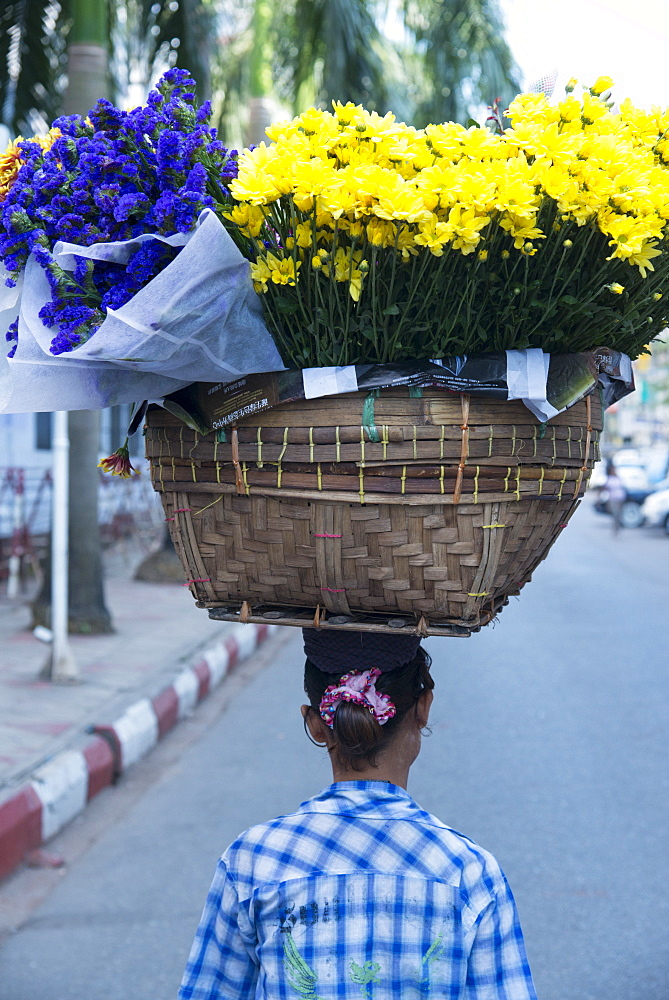 Woman carrying large flower basket on her head, Yangon (Rangoon), Myanmar (Burma), Asia