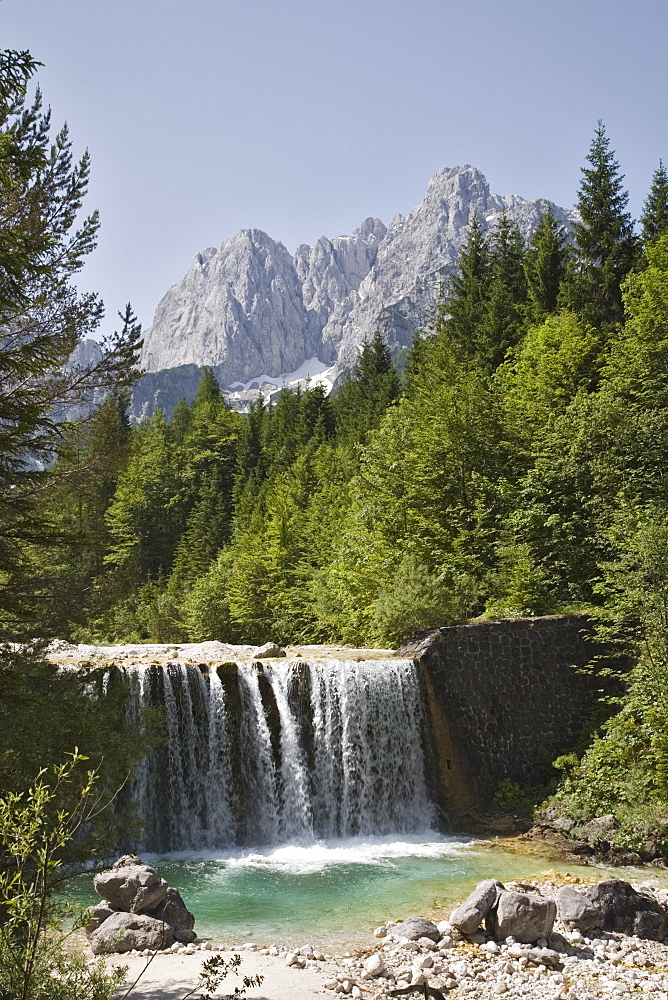 View across waterfall over weir on River Velika Pisnca to Prisank mountain, Triglav National Park, Julian Alps, Kranjska Gora, Dolina, Slovenia, Europe