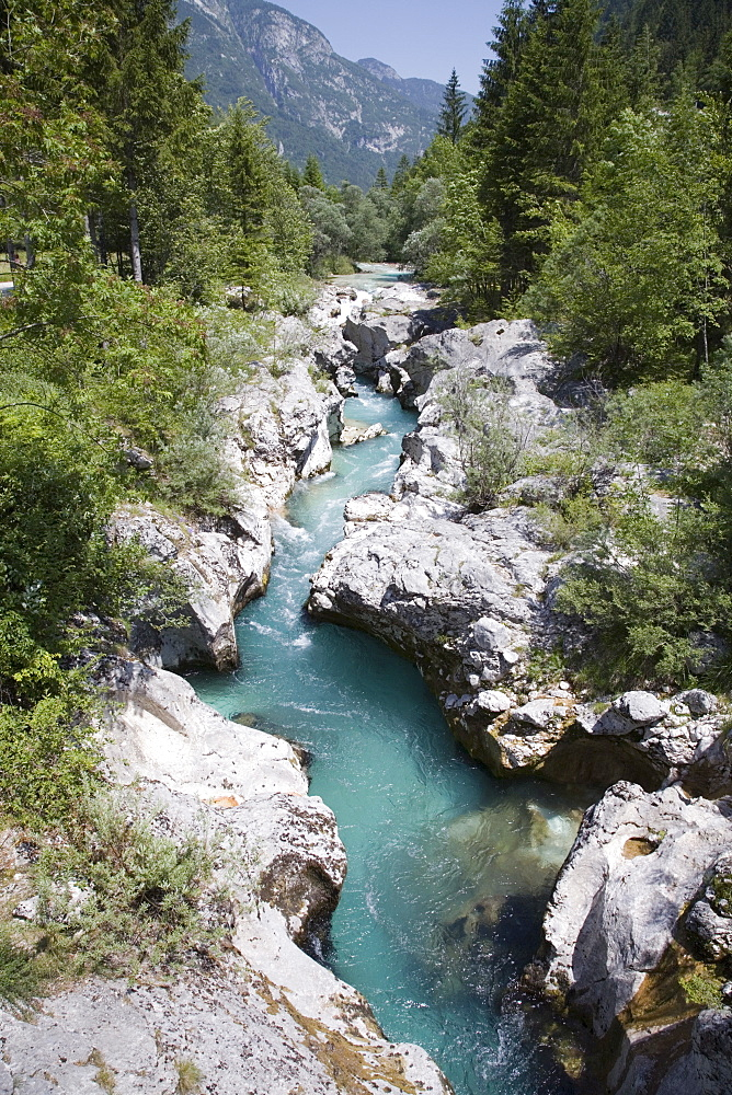 Soca River with clear emerald water flowing between eroded rocks in Trenta Valley in summer, Triglav National Park, Julian Alps, Slovenia, Europe
