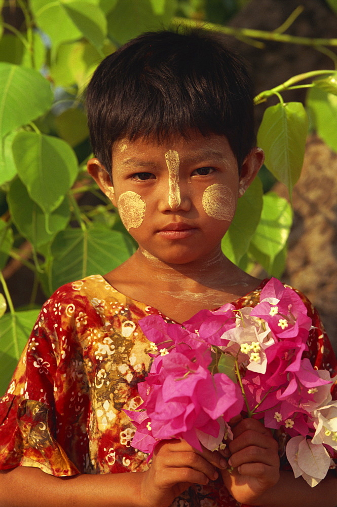 Head and shoulders portrait of a young Burmese girl with short hair and sandalwood Thanaka facial decoration, holding a bunch of flowers, Bagan (Pagan) area, Myanmar (Burma), Asia